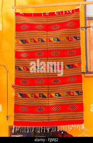 Colorful Souvenir Orange Mexican Blanket Yellow Adobe Wall San Miguel de Allende Mexico - Stock Photo