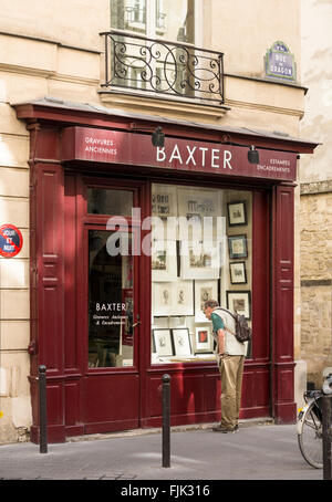 Man looking at antique prints in shop window on the Rue du Dragon in the trendy Saint Germain district, Paris, France - Stock Photo