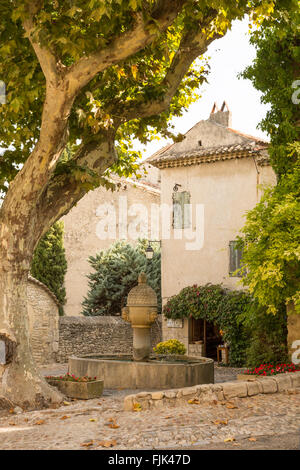 A stone fountain is shaded by an ancient plane tree in the historic Medieval village square, Vaison la Romaine, - Stock Photo