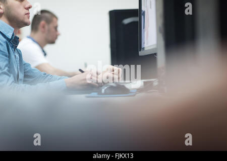 photo editors working with graphic tablet and pen on photographs in retouching studio - Stock Photo