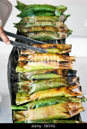 Woman cooking sticky rice wrapped in banana leaves on a market stall in Khao Sok, Thailand - Stock Photo