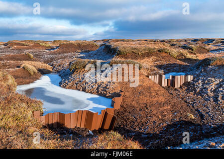 Water held back by a plastic dam due to gully blocking on moorland, now frozen into ice during Winter, Kinder Scout, - Stock Photo