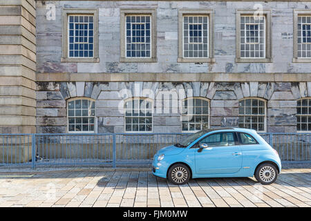 A blue fiat 500 car parked in front of an interesting building - Stock Photo