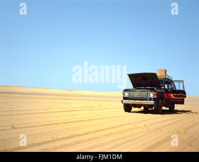 Broken down 4WD in the Arab desert with the hood raised - Stock Photo