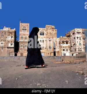 A veiled Muslim woman walks on a Sana a street, Yemen.At background typical Yemen houses. - Stock Photo