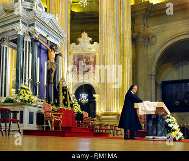 Malaga, Spain - April 18, 2011:Roman Catholic nun preparing the altar for the service, in the Cathedral, of Malaga, - Stock Photo
