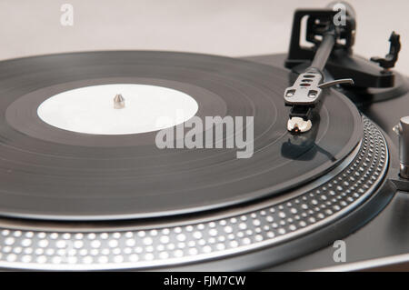 Old style vinyl record spinning on a turntable - Stock Photo