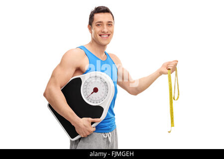 Cheerful athlete holding a weight scale and a measuring tape isolated on white background - Stock Photo