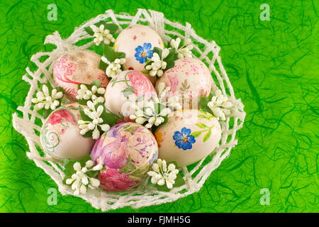 Colorful decoupage decorated Easter eggs in a basket - Stock Photo