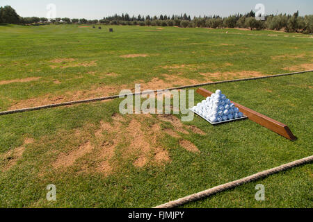 Golf driving range with pyramid of balls tee divots and ready to practice - Stock Photo