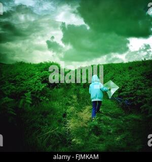 Rear View Of Boy In Hood With Kite Walking On Green Landscape Against Cloudy Sky - Stock Photo