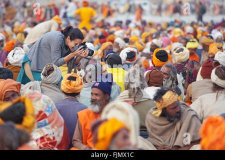 Tourist photographing sadhus (holy men) at Maha Kumbh Mela, the largest Hindu festival in India. - Stock Photo