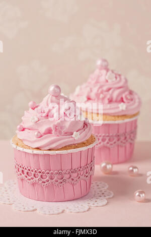 Pink cupcakes on a beige background - Stock Photo