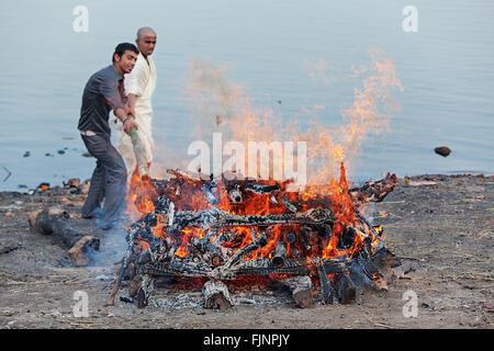 Cremation fire at the bank of holy Ganges river. Varanasi, India. - Stock Photo