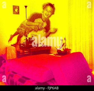 Boy Jumping On Bed - Stock Photo