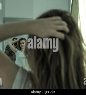 Man Photographing Woman With Hand In Hair While Reflecting On Mirror At Home - Stock Photo