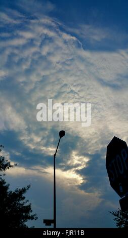 Low Angle View Of Road Sign And Street Light Against Cloudy Sky - Stock Photo