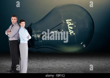 Business people standing in front of light bulb - Stock Photo