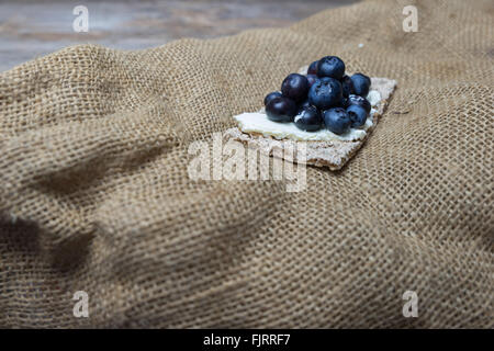 fresh blueberries on crispbread with cream cheese - Stock Photo