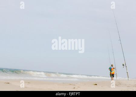 Full Length Rear View Of Fisherman Standing On Beach With Rods Against Sky - Stock Photo