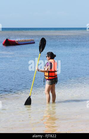 Woman Wearing Life Jacket While Holding Oar On Sea - Stock Photo