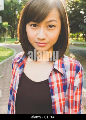 Portrait Of Confident Woman In Park - Stock Photo