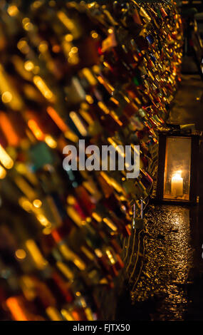 Love Padlocks On Fence Against Lit Candle At Night - Stock Photo