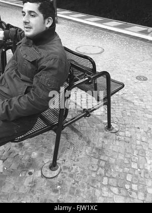 High Angle View Of Man Sitting On Bench At Street - Stock Photo