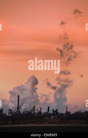 Smokestacks from oil refinery emitting gases into air at sunset - Stock Photo