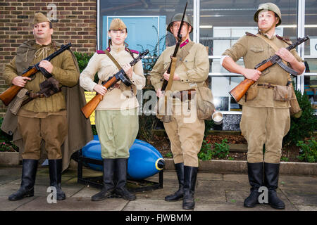 World War two Re-enactment. Four Russian soldiers standing facing viewer, posing, three men, one woman holding rifles - Stock Photo