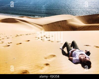 High Angle View Of Woman Relaxing On Desert By Sea - Stock Photo