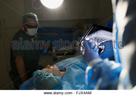 Plastic surgeon preparing patient for surgery operating room - Stock Photo
