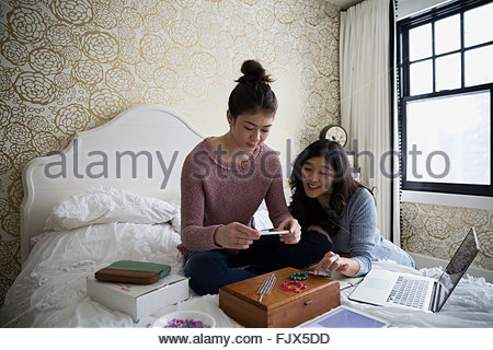 Mother and teenage daughter photographing homemade jewelry - Stock Photo