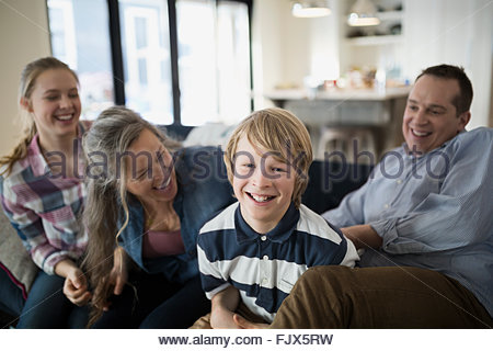 Portrait smiling boy with family living room sofa - Stock Photo