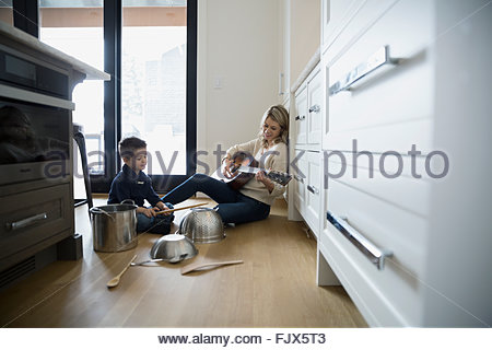 Mother playing guitar and son banging kitchen pots - Stock Photo