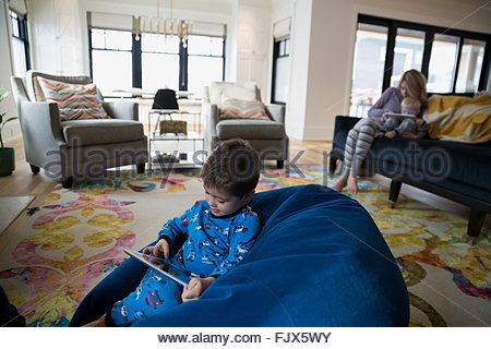 Boy pajamas using digital tablet bean bag chair - Stock Photo