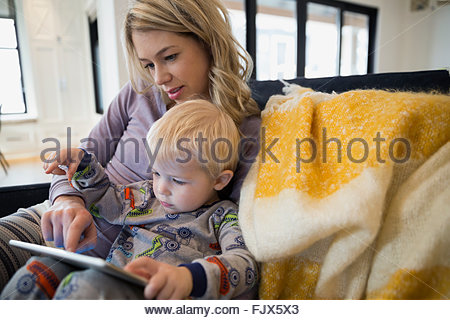 Mother and son in pajamas using digital tablet - Stock Photo