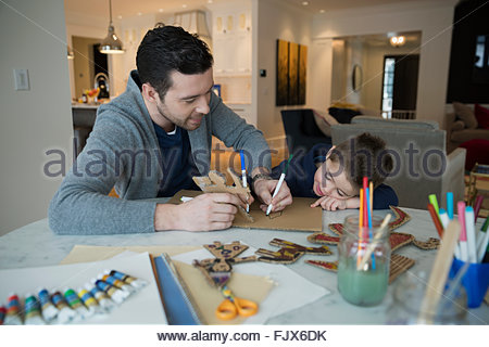 Father and son drawing with markers at table - Stock Photo