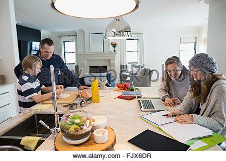 Family baking and doing homework at kitchen island - Stock Photo