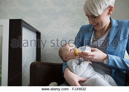 Mother feeding baby son with bottle - Stock Photo