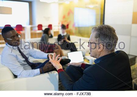 Businessmen talking in office lobby - Stock Photo