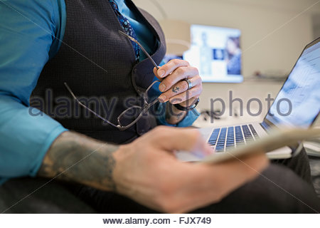 Close up businessman with tattoos using laptop - Stock Photo