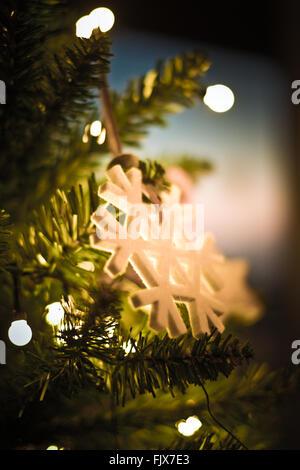 Close-Up Of Snowflake Hanging On Illuminated Christmas Tree - Stock Photo