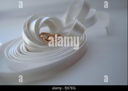High Angle View Of Wedding Rings On Ribbon On Table