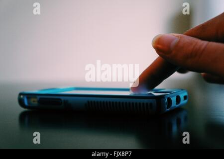 Cropped Image Of Woman Finger Touching Smart Phone - Stock Photo
