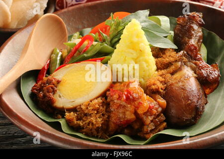 Nasi Kuning, Javanese turmeric rice with variety of side dishes; plated on earthenware crockery. - Stock Photo