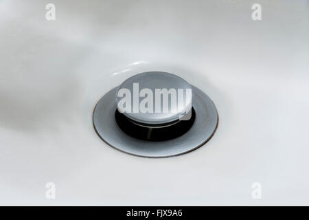 Built in bathroom sink drain stopper in the open position. - Stock Photo