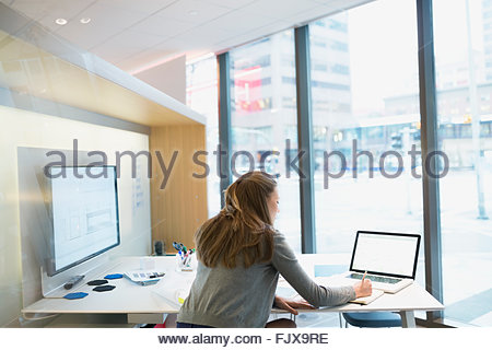 Young businesswoman using laptop in urban office - Stock Photo