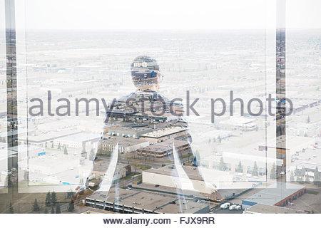 Digital composite businessman looking over industrial buildings - Stock Photo