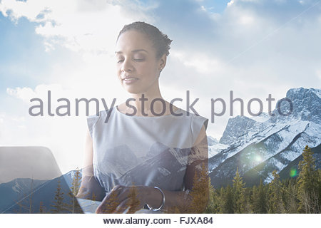 Digital composite businesswoman using laptop against mountains - Stock Photo